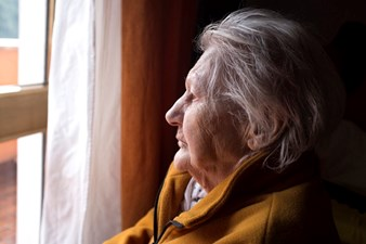 Sad old lady looking out of window