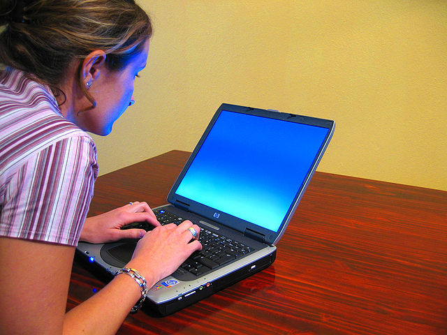Woman typing at laptop