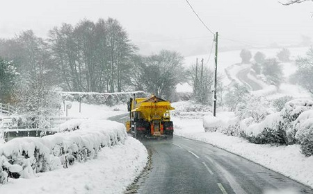 Gritter lorry on country lane in snow