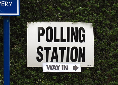 Polling station sign stuck to hedge