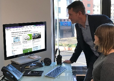 Two people looking at East Herts intranet on screen