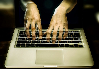 Ghostly hands on laptop keyboard