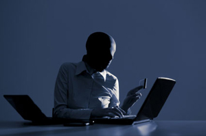 Man in shadow with laptop