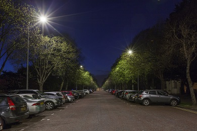 LED lamposts in quiet street with parked cars
