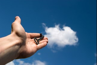 Hand holding key towards cloud