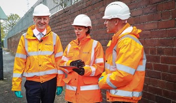 Oliver Dowden, Heidi Mottram, Clive Surman Wells in yellow jackets and hard hats