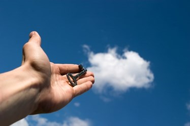 Hand holding key towards a cloud