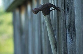Hammer and nail in fence