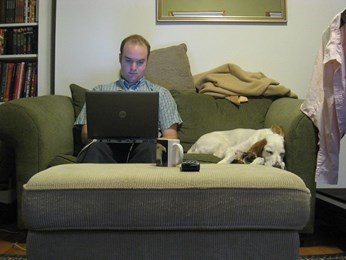 Man with laptop on sofa and dog beside him