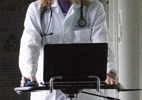 Woman in white coat with laptop