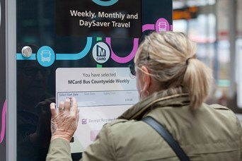 Woman looking at MCard sign